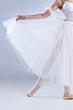 Beautiful ballerina posing, on gray studio background