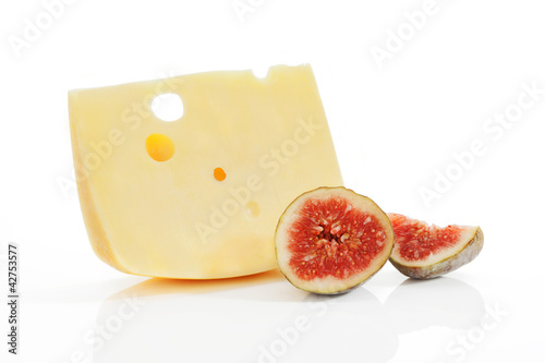 Emmental piece with fig on white.
