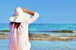 Jeune femme qui tient son chapeau au bord de l'eau