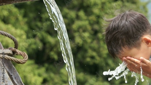 Boy refreshing his face in stream of water. Slow Motion.