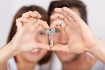 junges paar hält wohnungsschlüssel in der hand
