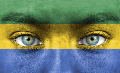Human face painted with flag of Gabon