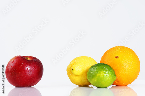 Apple compared to citrus fruits over white