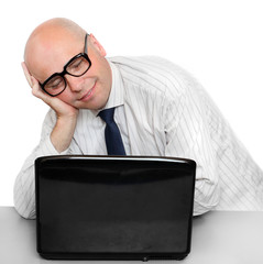 Sleeping businessman with laptop on a desk in office.
