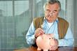 Senior steckt Geld in Sparschwein