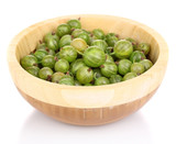 Green gooseberry in wooden bowl isolated on white