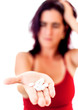 Woman extending her hand full of pills isolated on white
