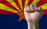 us state flag of arizona with hard fist in front of it symbolizi