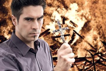 Mann mit Kreuz vor Feuerinferno