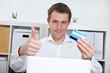 Geschäftsmann mit Kreditkarte hält Daumen hoch