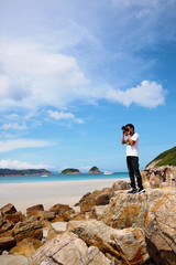 Portrait of a young man standing on a beach with a camera