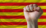 Hard fist in front of catalonia flag symbolizing power
