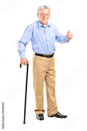 Mature man walking with cane and giving a thumb up