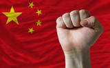 Hard fist in front of china flag symbolizing power