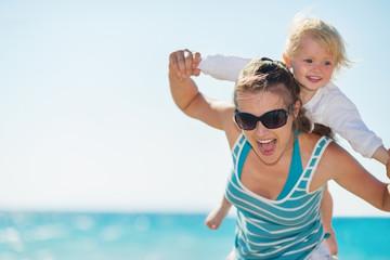 Baby piggybacking mother on beach