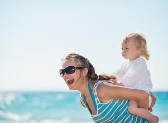 Kid piggybacking mother on beach