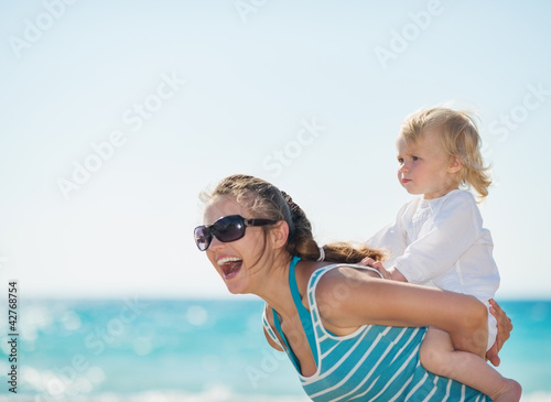 Kid piggybacking mother on beach