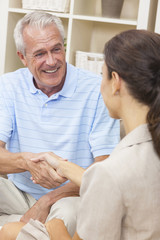 Saleswoman Shaking Hands With Senior Man at Home