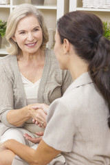 Saleswoman Shaking Hands With Senior Woman at Home
