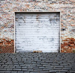 old roll up garage door on brick wall