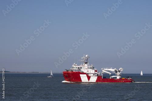 Leinwanddruck Bild supply ship leaving the harbour