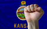 us state flag of kansas with hard fist in front of it symbolizin