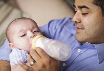 Happy Hispanic Father Bottle Feading His Son