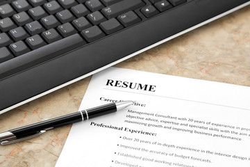 Closeup of Resume with Pen and Keyboard on the Table