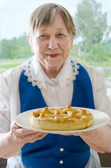 Happy smiling senior woman showing her apple pie