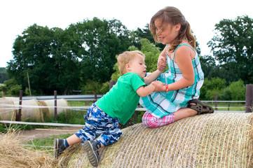 Kinder klettern auf Heuballen