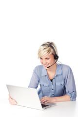 blonde frau mit headset schaut auf laptop