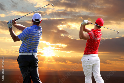 Men playing golf against sunset - 42786513