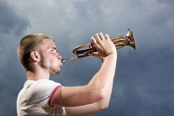 The young man blows the trumpet