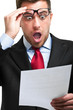 Shocked businessman while reading an expensive bill