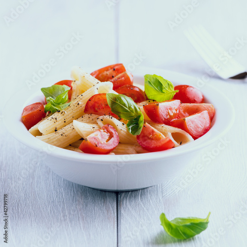 Bowl of pasta salad with cherry tomatoes and basil