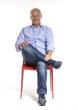 Señor  alegre sentado en una silla roja.