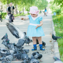 two-year girl feeding doves