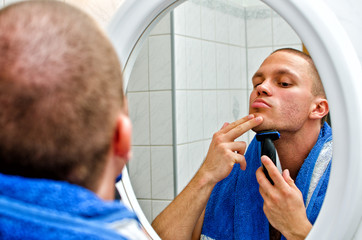 Male with towel shaving in bathroom in front of the mirror.
