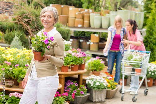 Garden center senior lady hold potted flower