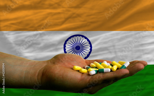 holding pills in hand in front of india national flag