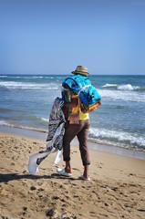 Venditore ambulante di tappeti cammina lungo la spiaggia