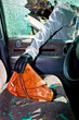 Ein Dieb entwendet eine Handtasche aus Auto