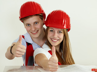 Young worker  fixing up a house and showing thumbs up