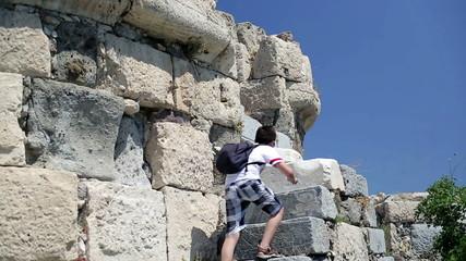 Young teenager climbing up ancient wals