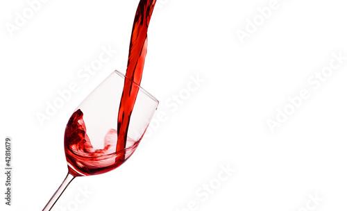 Rotwein wird in ein Weinglas eingegossen