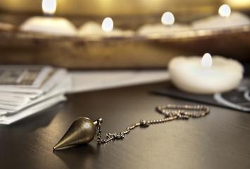 Pendel mit Tarotkarten und vielen Kerzen