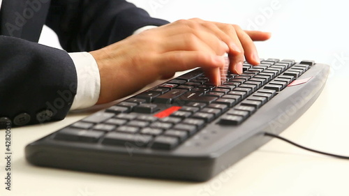 hands in official suit typing on keyboard