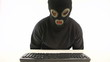 guy in balaclava typing something on the keyboard