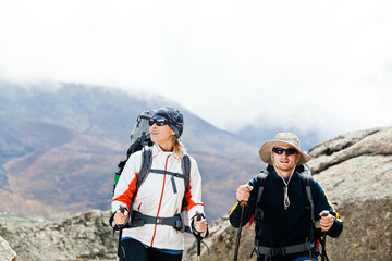 Couple hiking in mountains, man and woman trekking
