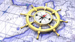 Compass in a ship's wheel over a map